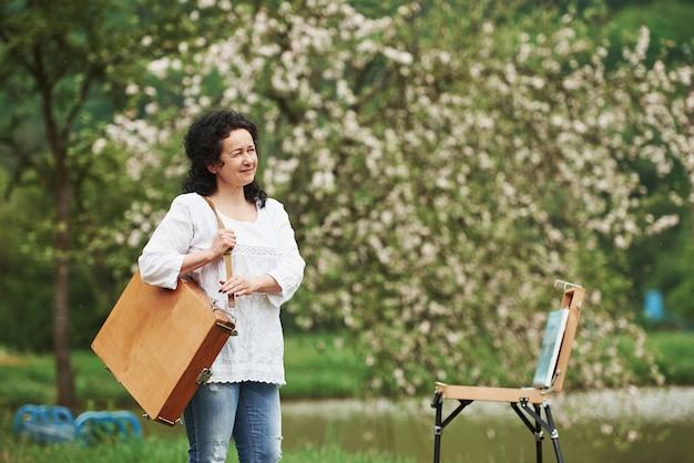한 사람 만. 악기 케이스를 든 성숙한 화가가 아름다운 봄 공원에서 산책