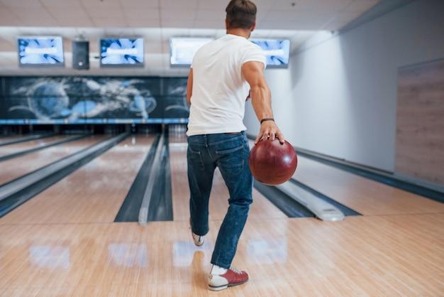 Una sola persona. vista posteriore dell'uomo in abiti casual, giocare a bowling nel club