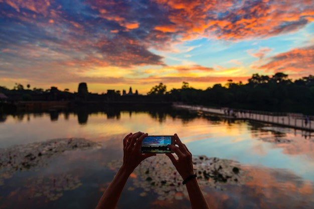 One person photographing angkor wat main facade silhouette at dawn holding smart phone