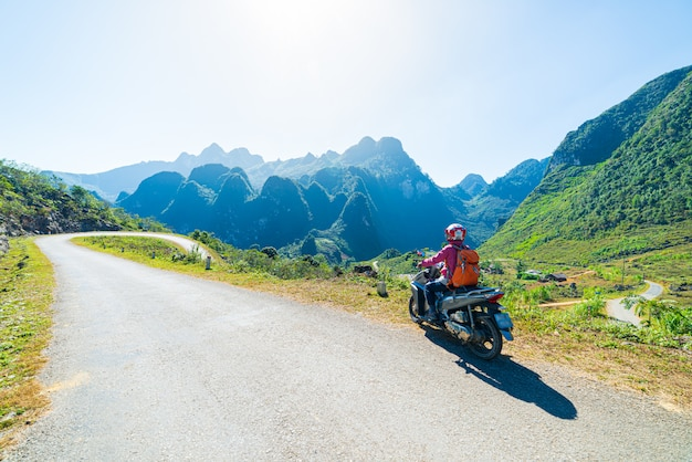 One person riding bike on ha giang motorbike loop, famous travel destination bikers easy riders. ha giang karst geopark mountain landscape in north vietnam. winding road in stunning scenery.