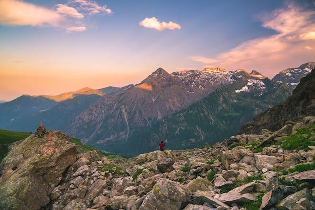 One person sitting on rocky terrain and watching a colorful sunrise high up in the alps.