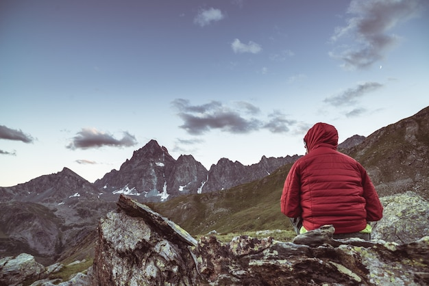 One person sitting on rocky terrain and watching a colorful sunrise high up in the alps