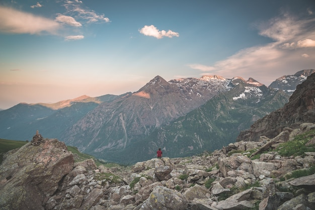 One person sitting on rocky terrain and watching sunrise high up in the alps