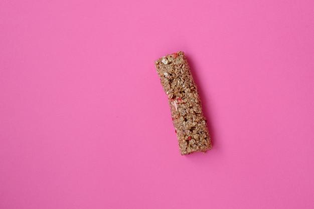 글루텐이 없는 그라놀라 시리얼 스낵, 씨앗, 말린 과일이 포함된 단백질 에너지 바, 다양한 견과류, 분홍색 배경. 건강한 비건 슈퍼 푸드, 피트니스 다이어트 간식, 스포티한 라이프 스타일. 상위 뷰 전단지