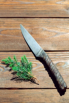One piece metal knife made of metal crane rope on wood.
