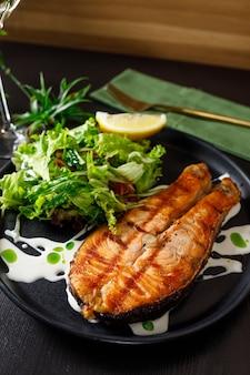 Один кусок запеченного лосося на гриле с перцем, лимоном и солью на черной тарелке с листьями салата на каменном фоне