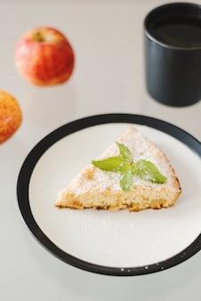 검은색 테두리가 있는 흰색 접시에 제공되는 간단한 홈메이드 애플 파이 한 조각