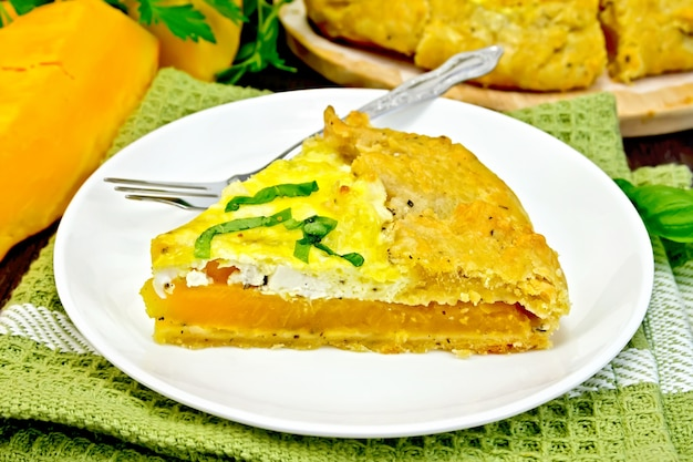 カボチャ、塩味のフェタチーズ、卵、クリーム、ハーブのパイの一部をタオルの皿に、バジルを暗い木の板に