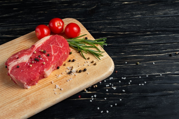 One pieces of juicy raw beef on a cutting board on a black wooden table