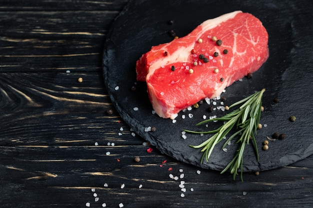 One pieces of juicy raw beef on a stone cutting board on a black wooden table background.