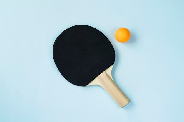 Одно весло для пинг-понга и мяч на синем фоне