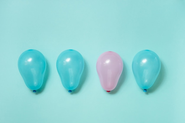 One pink balloon among many blue balloons on blue background. gender equality concept