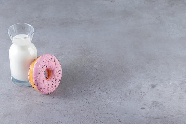 Una ciambella rosa con codette e una brocca di vetro di latte fresco.