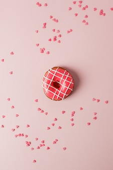 One pink live colar donut and heart shaped sprinkles on pink background, monochrome