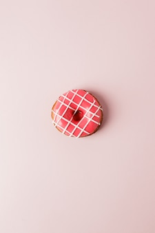 One pink live colar donut on pink background, monochrome seet unhealthy food concept, flat lay