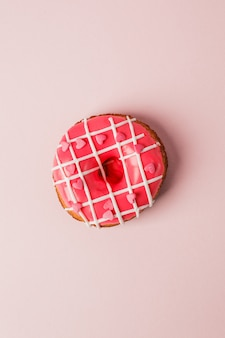 One pink live colar donut with heart shaped sprinkles on pink background, monochrome
