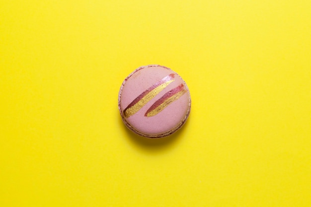 光沢のある金色の縞模様のピンクのマカロンまたはマカロンが黄色の上にあります