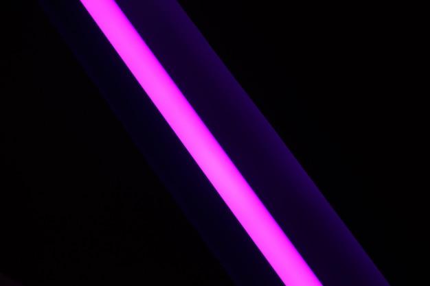 黒の背景に斜めに行く1つのピンクのネオンストリップ。