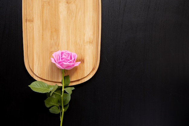 One pink rose lays on a wooden chopping board on a dark backgrou