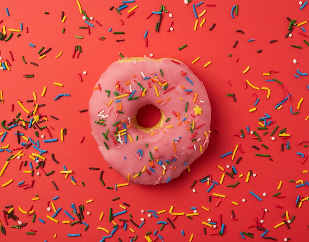 One pink round donut with colored sprinkles on a red background