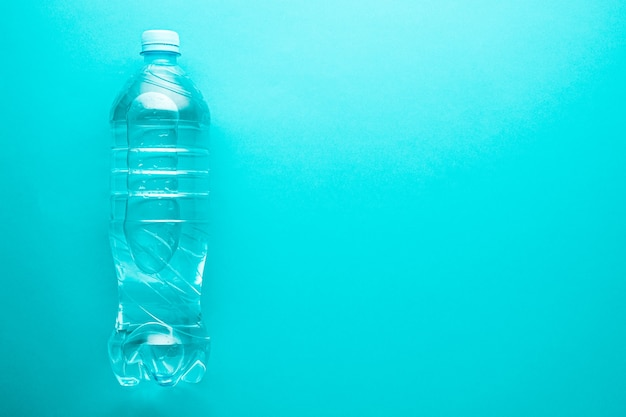 One plastic clean water bottle with copy space on neo mint background