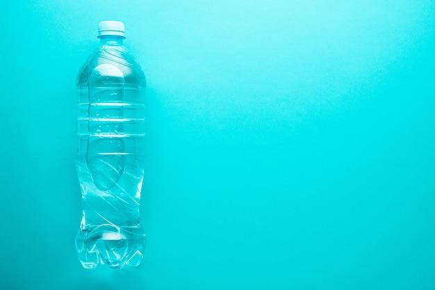 ネオミントの背景にコピースペースのあるプラスチック製のきれいな水ボトル1本