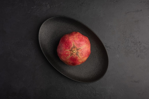 One pomegranate in the peel served in black oval plate on moody dark background. top view, healthy diet concept, copy space