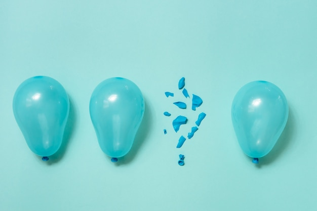 One popped balloon among other whole blue balloons on blue background. b