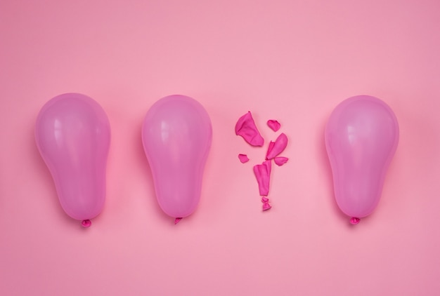 One popped balloon among other whole pink balloons on pink table. burnout or being under pressure concept. top view flat lay.