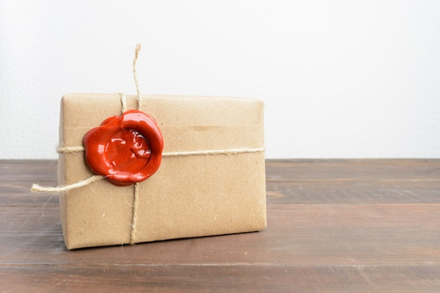 One present in craft paper with red sealing wax over wooden table