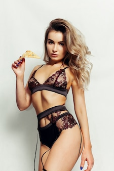 피자의 맛있는 큰 조각을 들고 긴 큰 끈 머리와 검은 속옷에 한 꽤 젊은 섹시한 여자