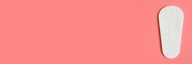 ピンクの背景に1つの純粋な女性の使い捨ての毎日の月経生理用ナプキンまたはナプキン