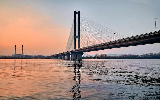One-pylon cable-stayed bridge over the city river at sunset.