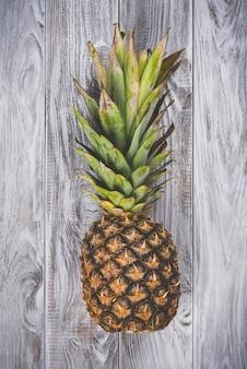 Один необработанный ананас на белом деревянном столе.