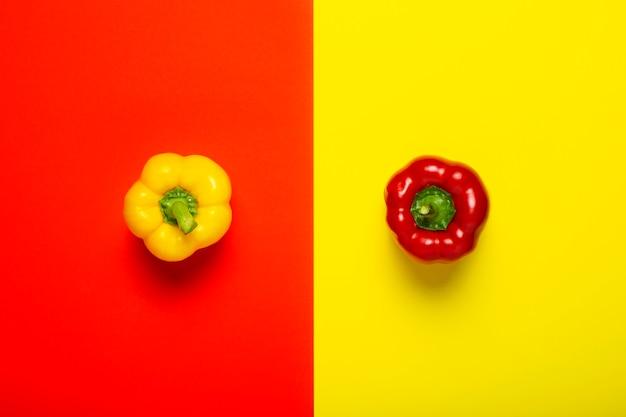 Один красный и желтый перец на желто-красном фоне. вид сверху, плоская планировка.