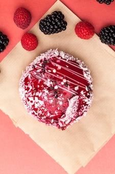 Один красный торт со сливочно-белой начинкой, красное варенье с малиной и ежевикой