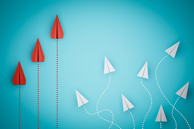 One red paper plane pointing in different way on blue background.