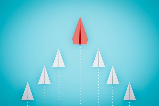 파란색 배경에 다른 방식으로 가리키는 하나의 빨간 종이 비행기.