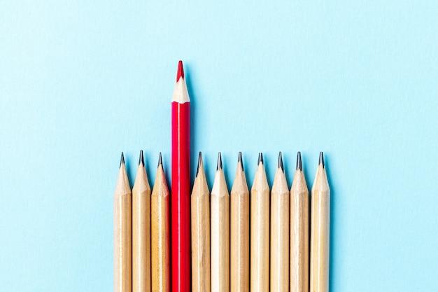 Один красный карандаш, выделяющийся из серии разноцветных карандашей.