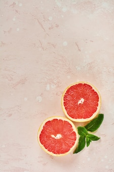 One red ripe grapefruit cut into two halves with mint leaves on a pink background. top view.