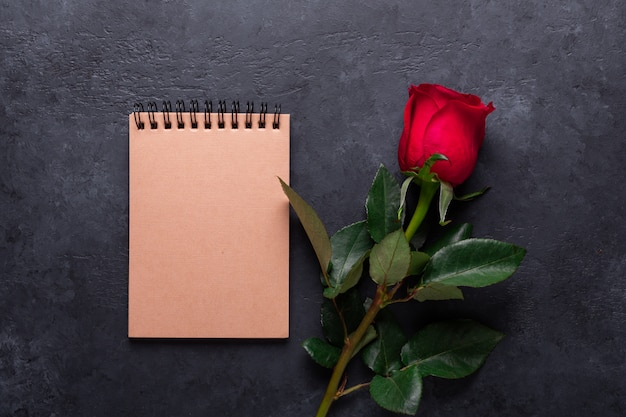 One red rose, notebook on black stone. valentine's day note with copyspace