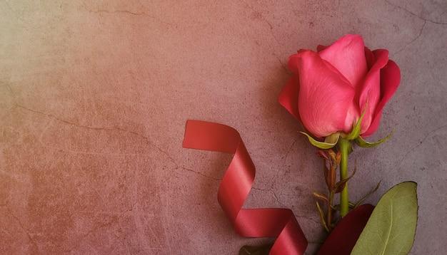 バーガンディのリボンが付いた濃い灰色の表面に1本の赤いバラ