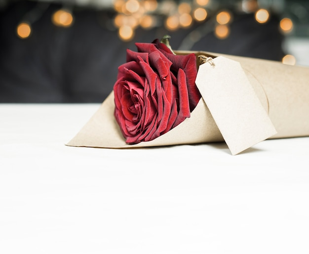One red rose wrapped in wrapping paper with label
