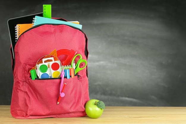 칠판 배경에 탁자 위에 있는 빨간 학교 배낭 하나와 녹색 사과