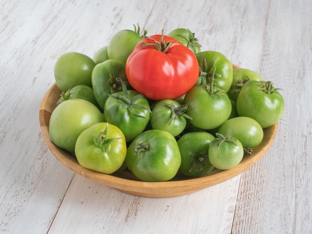 One red tomato among several green tomatoes on a wooden plate.