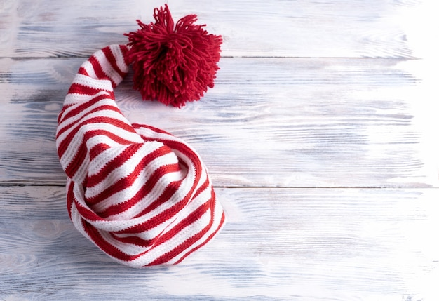 One red and white striped cap with a long tail and a large red pompom is on a white wooden table, flat lay, top view.