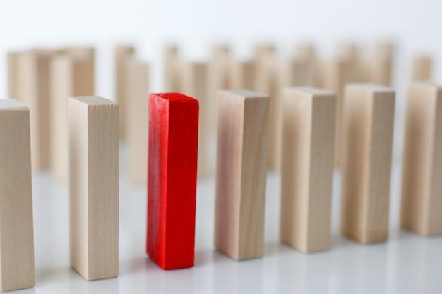 Один красный деревянный блок победителя, стоящий в ряду с идентичными