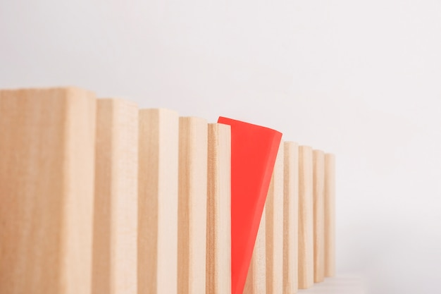 One red wood block is outstanding and stands out in the crowd. be different concept.