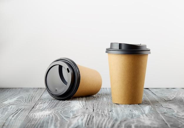 한 번의 휴식과 한 번의 비용으로 회색 나무 배경에 종이 커피 컵을 가져 가십시오.