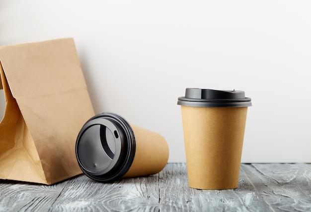 한 번의 휴식과 한 번의 비용으로 나무 배경에 점심 가방이 달린 종이 커피 컵을 제거합니다.